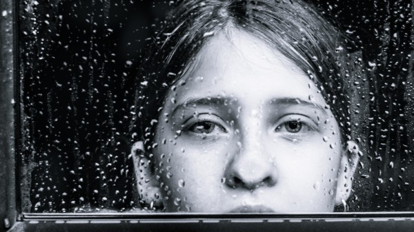 portrait of a girl staring out of the window longingly as it is raining