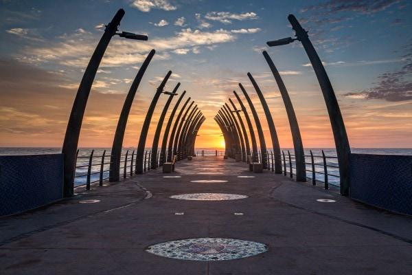 sunrise photo of a pier at the sea