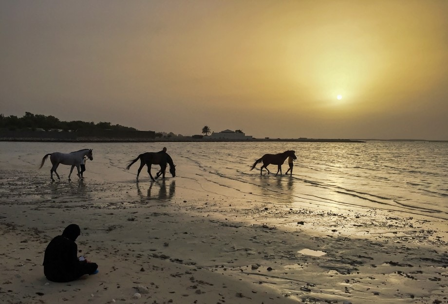travel photograph of muslim women praying during ramadan next to the arabian sea by deborah jordan