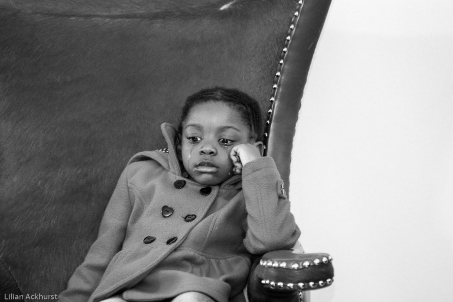 black and white photo of a child sitting in a chair and crying