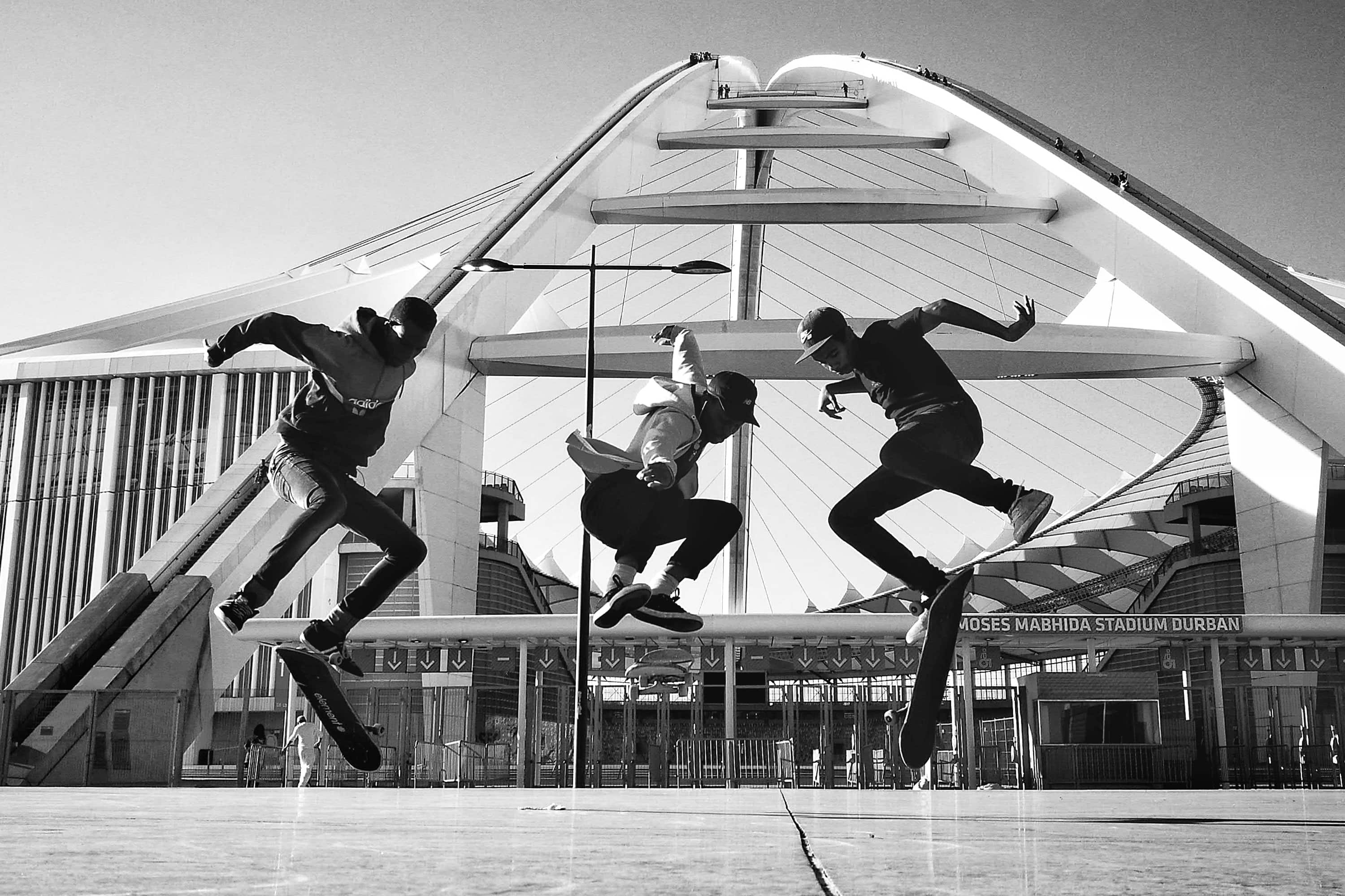 skateboarders synchronize their kick flips at the moses mabhida soccer stadium in durban, kzn