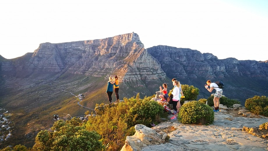 hikers greet a fresh sunrise on lions head featuring table mountain as an epic backdrop. cape town, western cape.