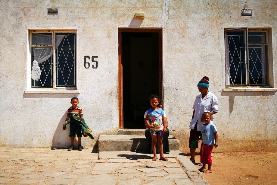 kids playing outside their homes pause and laugh with amusement at the photographer. springbok, northern cape