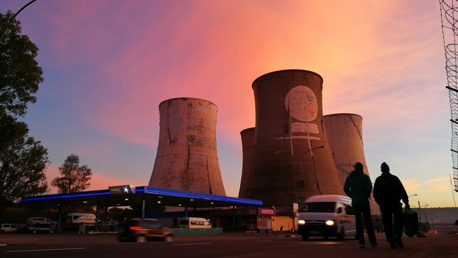 the cooling towers at a decommissioned power station stand as silent relics while pedestrians walk, and taxis rush, to work in bloemfontein, free state.