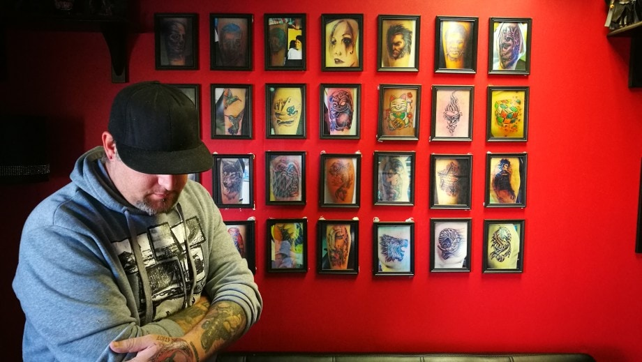 lee, a tattoo artist in bloemfontein, poses by a gallery of his work. free state.