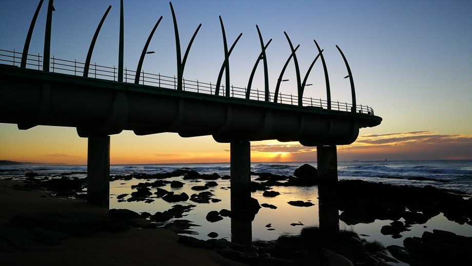 the world-famous pier at umhlanga rocks silhouetted against a postcard sunrise.